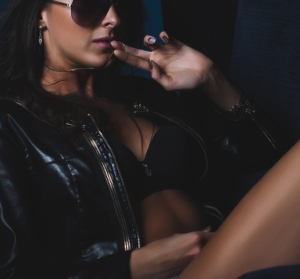 Sexy fashion brunette woman lying on blue armchair leather jacket and denim jeans shorts.